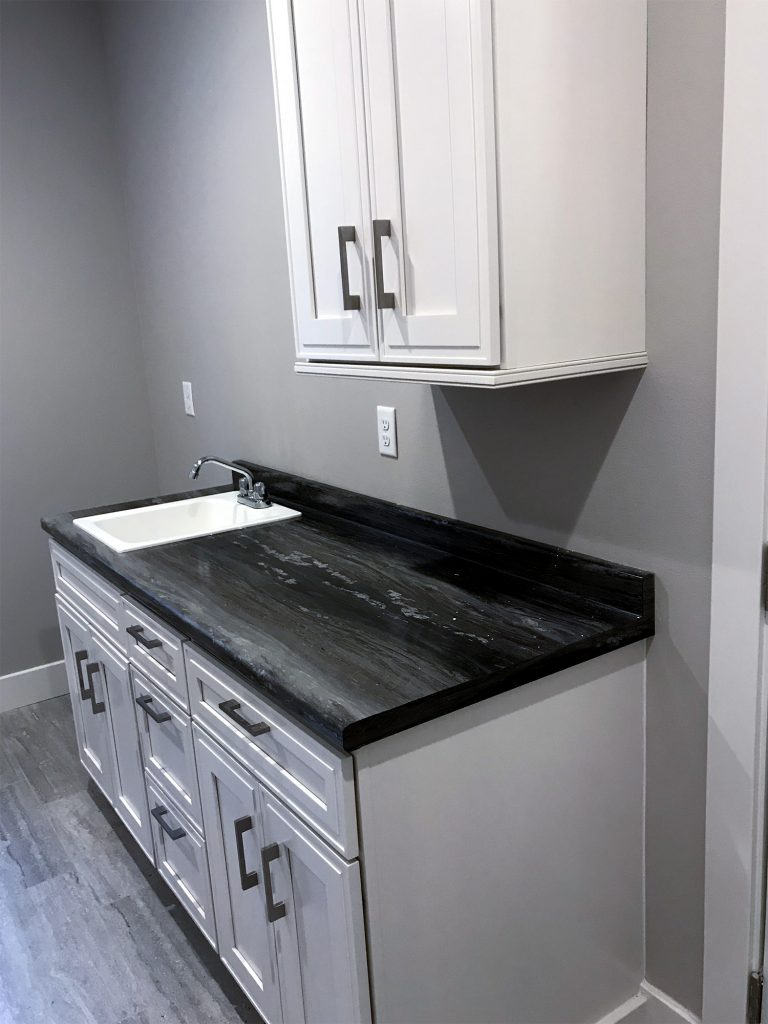Laundry room with dark countertop