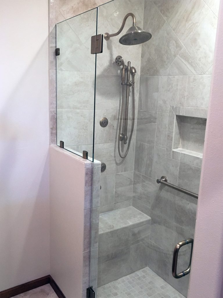 Light stone tile shower with glass surround