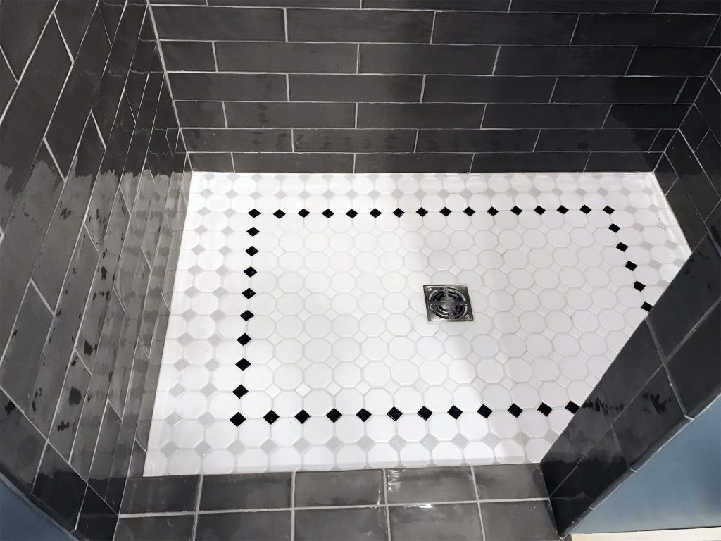 Dark gray shower tiles with light floor tiles
