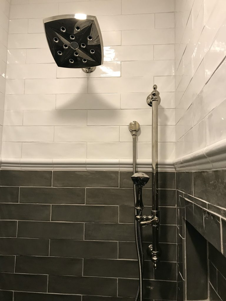 White and gray glass shower tiles with chrome fixtures