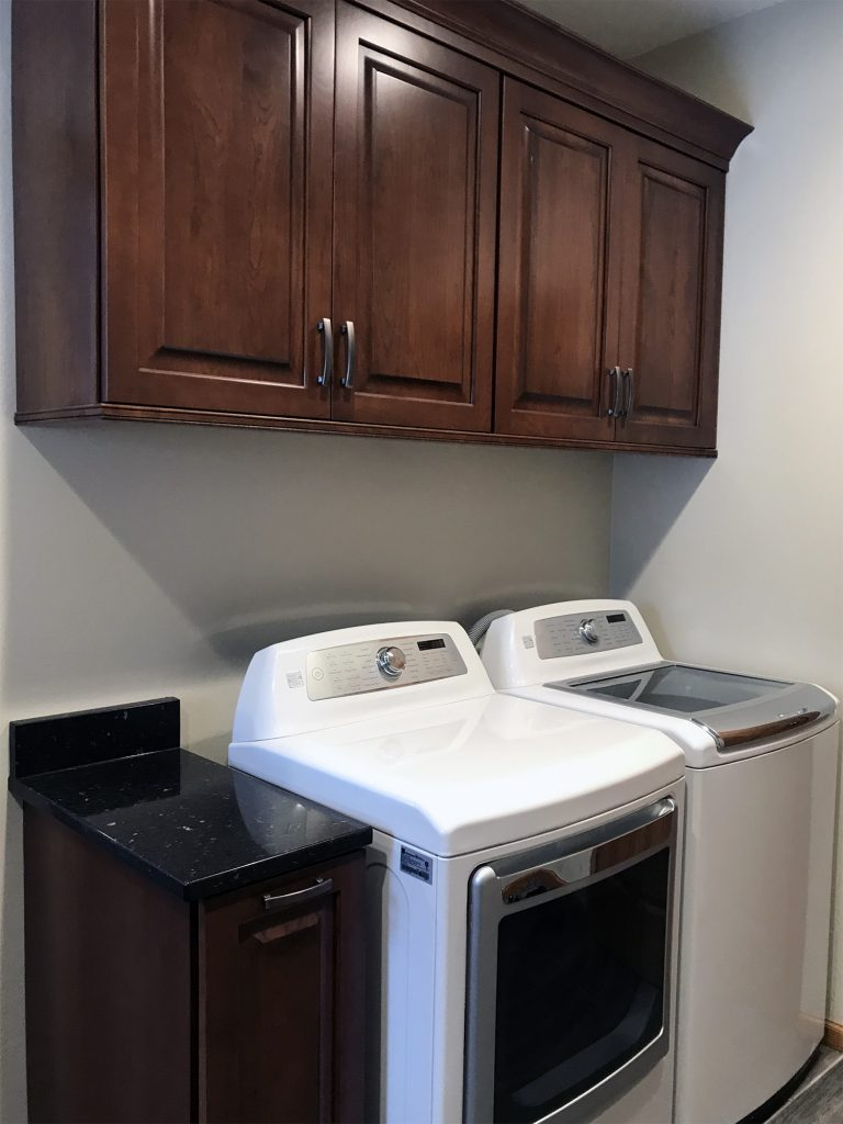 Laundry room with dark cabinets