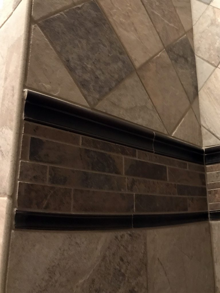 Light stone shower with glass inset