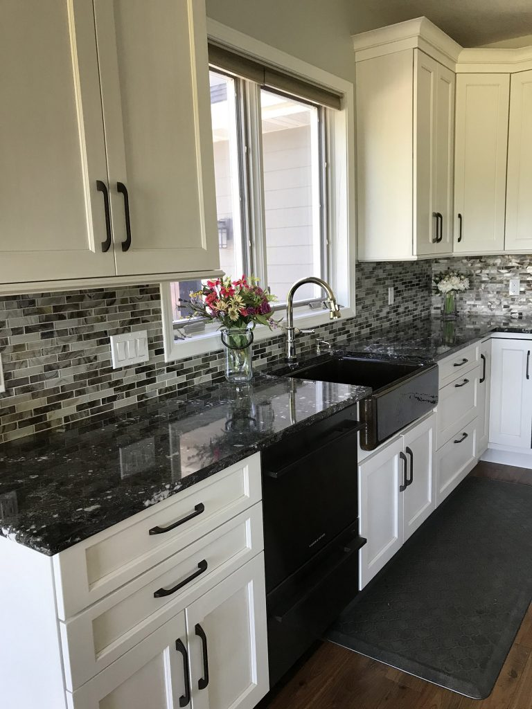 White kitchen cabinets with dark farmhouse sink