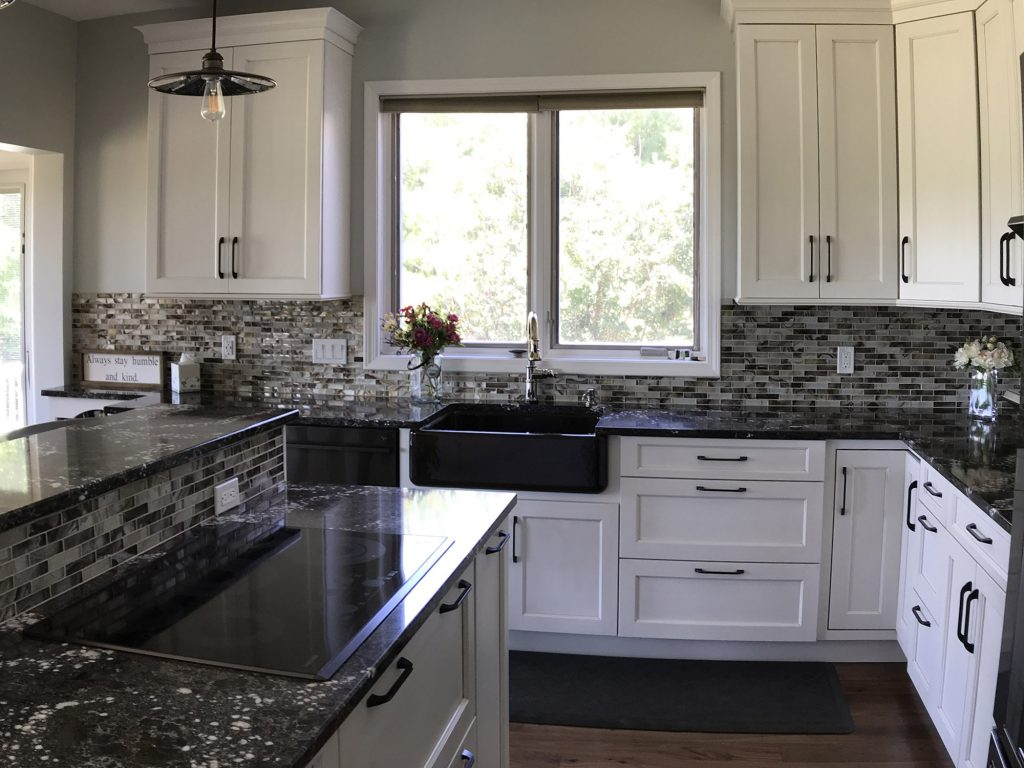 White kitchen with dark farmhouse sink, glass tile backsplash